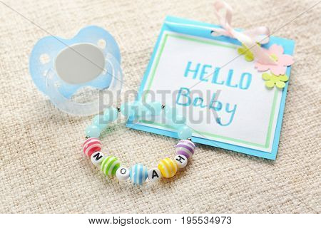 Bracelet with baby name NOAH, greeting card and pacifier on cloth