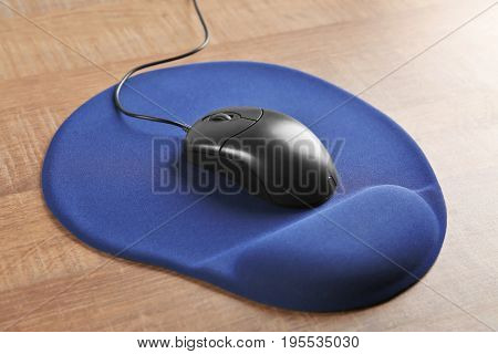 Blank mat and computer mouse on wooden background