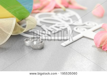 Beautiful composition with rings for lesbian wedding on gray background