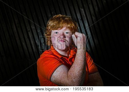Red-haired Boy Showing Biceps With Threaten Face