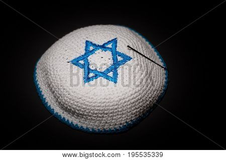 Knitted kippah with blue David star on black background close up. Seder concept.