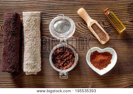 Composition of spa treatment. Coffee scrub, oil on wooden table background top view.