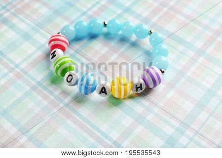Bracelet with baby name NOAH on color cloth