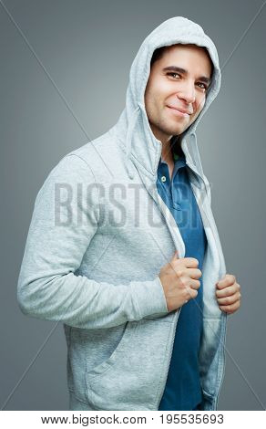 young handsome smiling man wearing a hood, isolated against gray background