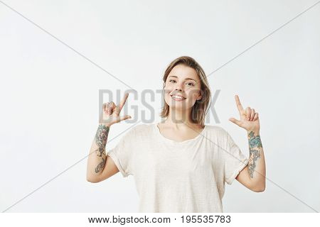 Happy sincere young girl pointing fingers up smiling looking at camera over white background. Copy space.