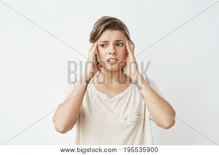 Young beautiful girl ashamed frowning with fingers on temples over white background. Copy space.