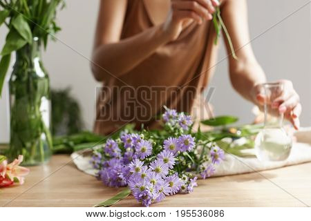 Close up photo of florist hands making bouquet of flowers at workplace.