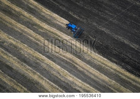 The tractor plows the field against the backdrop of the black earth, and behind it birds fly and collect food. Aeril view. Agricultural machinery works in the field of spring planting. Plowing from above.