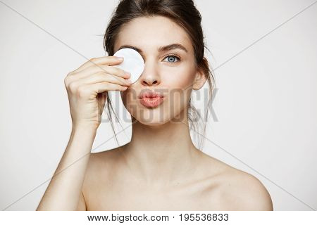 Beautiful natural brunette girl with clean perfect skin hiding eye behind cotton sponge smiling looking at camera over white background. Cosmetology and spa. Copy space.