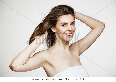 Beautiful young girl with perfect clean skin smiling looking at camera touching hair over white wall. Facial treatment. Copy space.