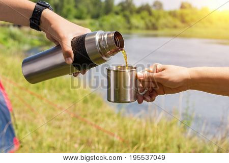 Pour The Tea From The Thermos Into A Mug .