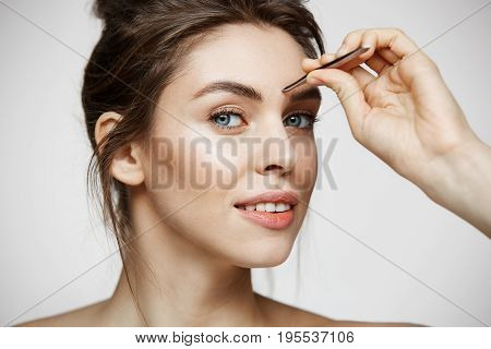 Young beautiful girl with perfect clean skin tweeze eyebrows looking at camera over white background. Facial treatment. Copy space.