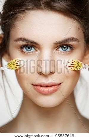 Close up portrait of beautiful young girl with perfect clean skin and alstroemeria petals looking at camera over white background. Facial treatment. Beauty and spa.