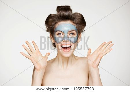 Beautiful surprised nude girl in hair curlers and facial mask looking at camera smiling over white background. Opened mouth. Beauty health cosmetology and skincare. Copy space.