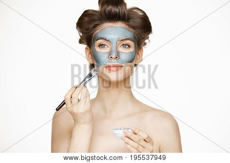 Young beautiful girl in hair curlers smiling covering face with mack. Facial treatment. Beauty cosmetology and spa. Copy space.