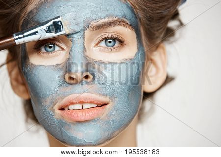 Close up photo of beautiful girl in hair curlers smiling looking at camera covering face with mack. Facial treatment. Beauty cosmetology and spa. Copy space.