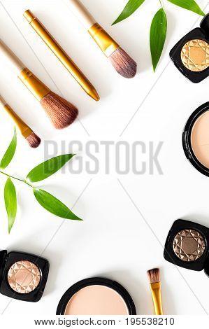Makeup kit. Eyeshadows, brushes, blushes on white table background top view.