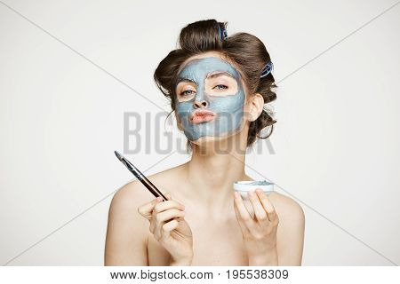 Young beautiful nude girl in hair curlers looking at camera covering face with mack. Facial treatment. Beauty cosmetology and spa. Copy space.