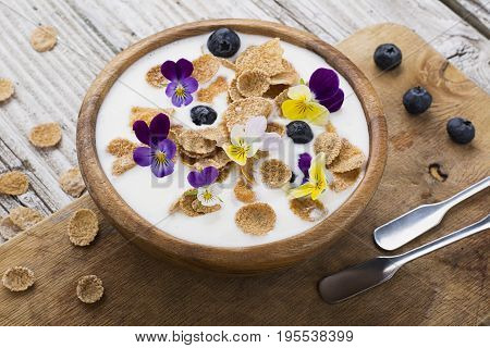 A wooden bowl with homemade breakfast: yoghurt, whole grains, blueberries, edible flowers of a garden viola on a simple wooden background. Top View
