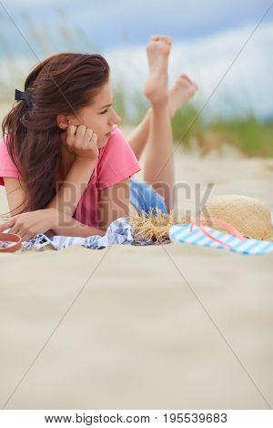 Brunette woman  lies on the sand on an empty beach