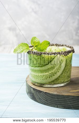 Fresh smoothies from cucumber, mint and honey in a glass are decorated with edible flowers of a garden viola. Selective focus