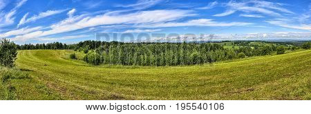 Bright summer rural landscape panorama with mown meadow hills forest blue sky and white clouds at nice sunny day. Fodder billet preparation for farm animals - agricultural concept