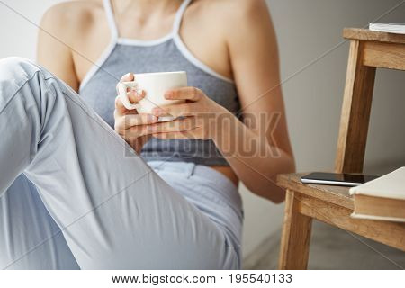 Close up photo of old books phone lying on chair, girl sitting on floor holding cup of coffee over white wall. Copy space.