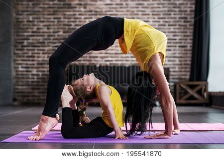 Adult woman and child girl practicing yoga together at home, adult standing in bridge pose and kid doing king cobra posture at home