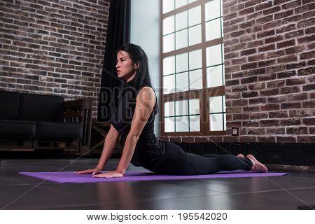 Female yoga beginner doing bhujangasana cobra pose on mat in loft apartment.