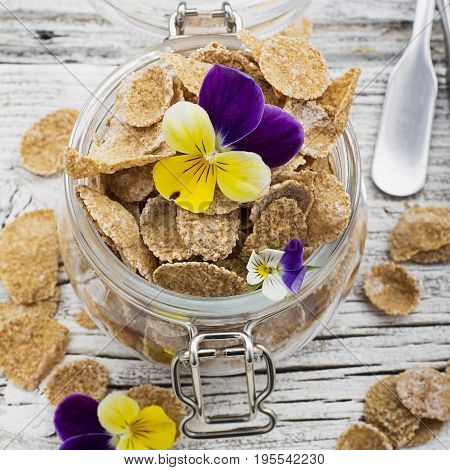 The concept of a healthy breakfast of whole wheat cereals, berries and edible flowers on a garden violet on a light wooden background in a glass jar. Selective focus.