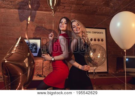 Two pretty women in cocktail dresses posing with balloons at birthday party in stylish cafe.