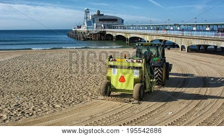 A tractor cleans the sand by raking it and picking up debri on the beach  at the english seaside town of Bournemouth