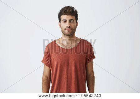 Portrait of stylish bearded guy with trendy haircut wearing casual red T-shirt looking with his brown eyes at the camera. Young handsome man having pleased look. People and emotions concept.