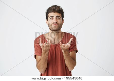 Studio portrait of attractive bearded student in red t-shirt stretching his hands to the camera. Emotional man with stylish hairstyle not understanding what is wanted from him.