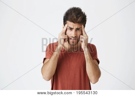 Studio shot of stylish bearded Caucasian man holding fingers on his temples with suffering expression, as if trying to remember something important or having headache.