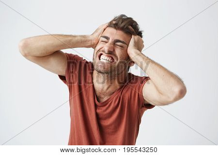 Emotional angry muscular man wearing red t-shirt closing eyes tight and screaming in pain or full disbelief, keeping hands on his head. Negative human emotions and feelings.