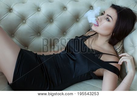 Woman releases smoke from her mouth she smokes lying down.