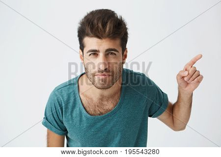 Cheerful young Caucasian male wearing blue t-shirt with stylish haircut pointing his index finger sideways at blank white copy space wall, indicating something extraordinary.