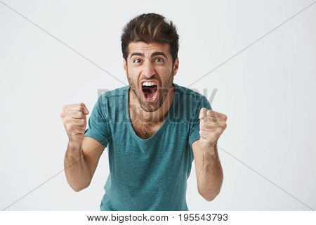 Emotions and achievement concept. Close up shot of happy successful casually weared student or employee screaming with winning expression, fists pumped, celebrating success on a white background.