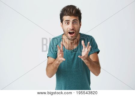 Crazy desperate good-looking man being shocked looking at camera with wide opened mouth and bugged eyes shouting with horror. Anxious male trembling with fear. Negative emotions and feelings concept.