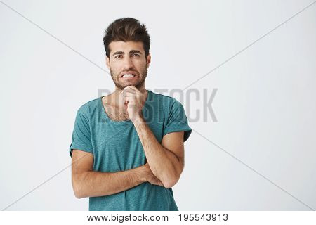 Human face expressions, emotions and feelings. Handsome young attractive man looking at the camera with thoughtful and skeptical expression, crossing his arms, trying to remember something.
