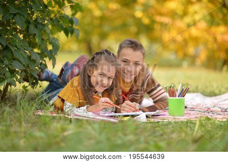 Brother and sister lying on green grass in autumnal park and drawing