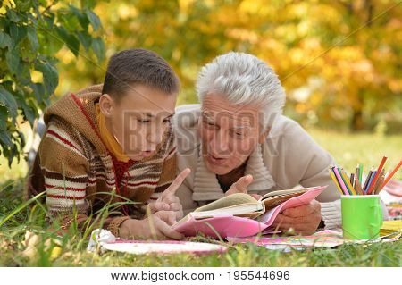 Grandfather and his grandson reading book outdoor