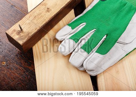 Working gloves lie on a log on a wooden background. The beginning of the carpenter's work