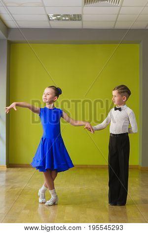 Boy and girl dancing ballroom dance in classroom