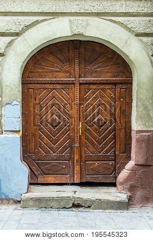 Front view closed doors. Old wooden decorative door in Lviv, Ukraine.