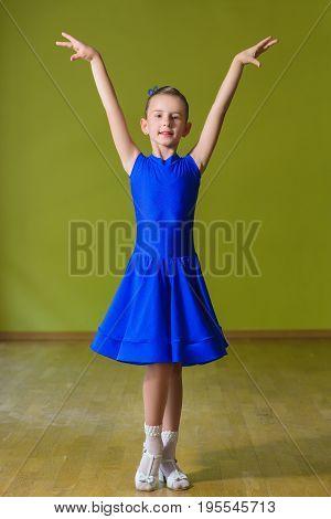 Little cute girl dancing ballroom dance in classroom
