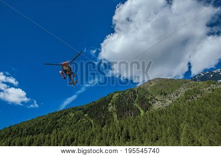 Argentière, France - June 27, 2016. Helicopter taking off in a forest at Argentière, a small alpine village with several ski routes in the winter and hiking in summer. Near Chamonix in the French Alps