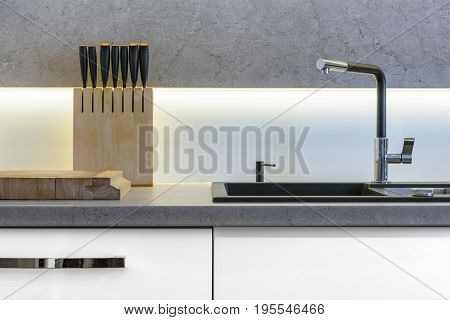 Detail of modern kitchen with knifes sink and wooden cutting board