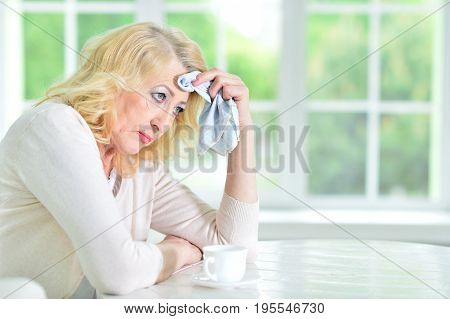 Portrait of sad mature woman sitting at table in kitchen